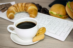 Cup of coffee and chocolate biscuits desk with computer Royalty Free Stock Photos