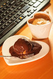 Cup of coffee and chocolate cake next to computer. Royalty Free Stock Images