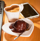 Cup of coffee and chocolate cake next to computer. Stock Image