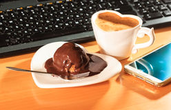 Cup of coffee and chocolate cake next to computer. Royalty Free Stock Photography