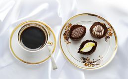 A cup of coffee and chocolate candies in a delicious plate on a white silk background Stock Photo
