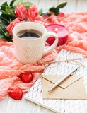Cup of coffee with chocolate candy. Cup of coffee with chocolate candies, roses and envelope stock image