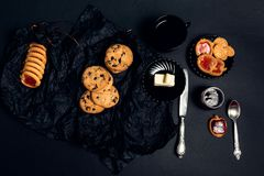 Cup of coffee with chocolate cookies and biscuits on black table background. Afternoon break time. Breakfast. Top view. Stock Images