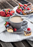 Cup of coffee and chocolate eclairs Stock Photos