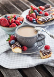 Cup of coffee and chocolate eclairs Royalty Free Stock Image