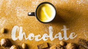 A cup of coffee and a chocolate inscription