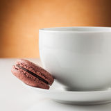 Cup of coffee with a chocolate macaron Stock Photo