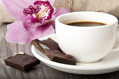 Cup of coffee, chocolate and orchid on wooden back Stock Images