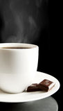 Cup of coffee with chocolate and saucer on black Stock Images