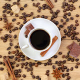 Cup of coffee, chocolate, sugar, spices and coffee beans on a wo Stock Images