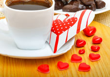 Cup of coffee with chocolate sweets a valentine heart on white p Stock Photos