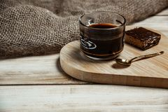 A cup of coffee with a chocolate waffle cake on a wooden heart-shaped tray.  royalty free stock image