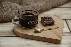 A cup of coffee with a chocolate waffle cake on a wooden heart-shaped tray.  royalty free stock photos