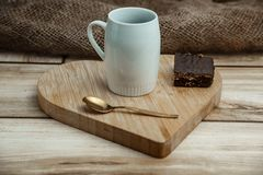 A cup of coffee with a chocolate waffle cake on a wooden heart-shaped tray royalty free stock image
