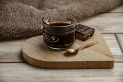 A cup of coffee with a chocolate waffle cake on a wooden heart-shaped tray.  stock images