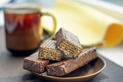 Cup of coffee, chocolate waffles with yellow napkin. Close-up. Horizontal royalty free stock photography
