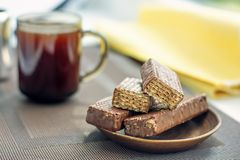 Cup of coffee, chocolate waffles with yellow napkin. Close-up. Horizontal royalty free stock image