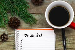 Cup of coffee christmas fir tree with cones and notebook with t. O do list on wooden background from above. Flat lay style Royalty Free Stock Photography