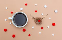 Cup of coffee with Christmas reindeer pompom on brown paper stock images