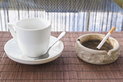 Cup of coffee and cigarette ashtray composition. Over a straw mat background Stock Image
