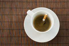 Cup of coffee and cigarette composition. Cup of coffee with the cigarette inside, composition over a straw mat background Royalty Free Stock Photography