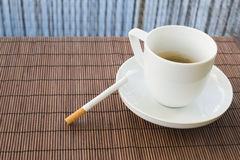 Cup of coffee and cigarette composition. Over a straw mat background Stock Images