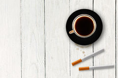 Cup of coffee with cigarettes on the wooden table Stock Images