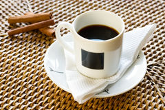Cup of coffee and cinnamon 2. White cup of coffee in rattan with cinnamon Royalty Free Stock Photography