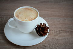 Cup of coffee with cinnamon and brown pine cones Stock Image