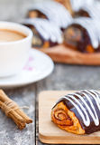 Cup of coffee with cinnamon buns glazed with chocolate Royalty Free Stock Images