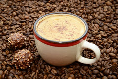 Cup of coffee with cinnamon and candies on a coffee beans background Royalty Free Stock Photography