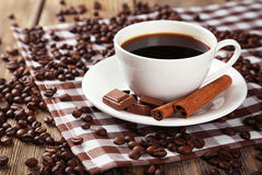 Cup of coffee with cinnamon and chocolate on brown wooden background. Royalty Free Stock Photography