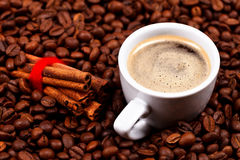 Cup of coffee with cinnamon on coffee beans Royalty Free Stock Image