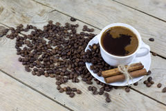 Cup of Coffee with Cinnamon and Coffee Beans on an old Wooden Table Royalty Free Stock Photos