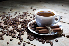 Cup of Coffee with Cinnamon and Coffee Beans on Wooden Table Royalty Free Stock Photos