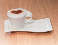 Cup of coffee with cinnamon heart on milk foam Stock Image