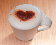 Cup of coffee with cinnamon heart on milk foam Stock Photos