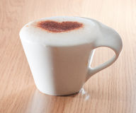 Cup of coffee with cinnamon heart on milk foam Royalty Free Stock Images