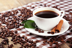 Cup of coffee with cinnamon and leaves on brown wooden background Stock Photography