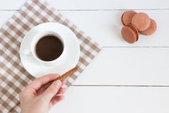 Cup of coffee with cinnamon in hand and macaroons on a white wooden background. Top view, copy space. royalty free stock photography