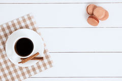 Cup of coffee with cinnamon and macaroons on a white background. Cup of coffee with cinnamon and napkin on a white background Stock Photo
