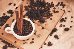 Cup of coffee and cinnamon on old book Stock Photography