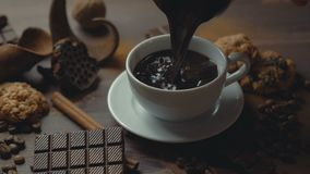 Cup of coffee cinnamon sticks, chocolate slices and anise star on old wooden table. stock video