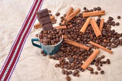 Cup of coffee with cinnamon sticks, bar of chocolate on vintage Royalty Free Stock Photo
