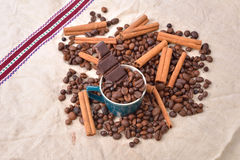 Cup of coffee with cinnamon sticks, bitten bar of chocolate on v Stock Images