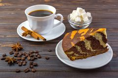 A cup of coffee with cinnamon sticks on a plate and a piece of tasty cake. Coffee beans. a bowl with sugar cubes and anise on wood Royalty Free Stock Photos
