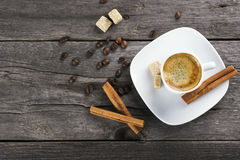 Cup of coffee with cinnamon and sugar on a wooden background.  Stock Photography