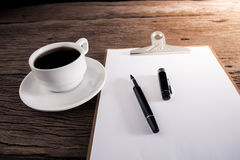 Cup of coffee and clipboard with blank page and pen Stock Photo