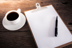 Cup of coffee and clipboard with blank page and pen Royalty Free Stock Photography