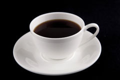 Cup of coffee close up. Coffee in white cup on black background Stock Photos